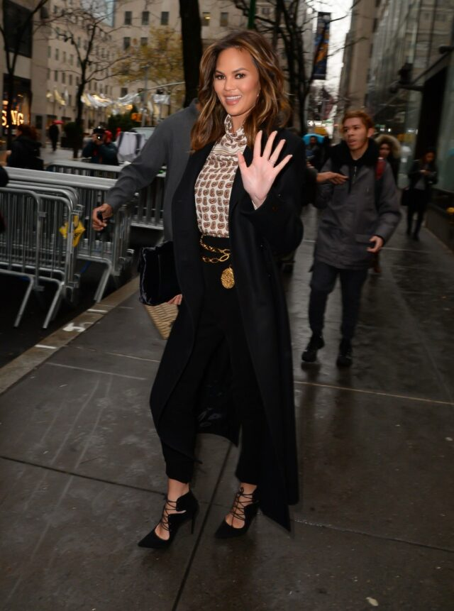 Image may contain Chrissy Teigen Clothing Apparel Human Person Coat Overcoat Footwear Shoe Sleeve and Long Sleeve