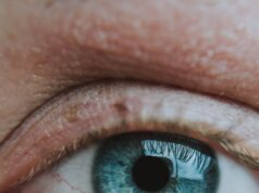 crop unrecognizable person with bright eye and rare eyelashes