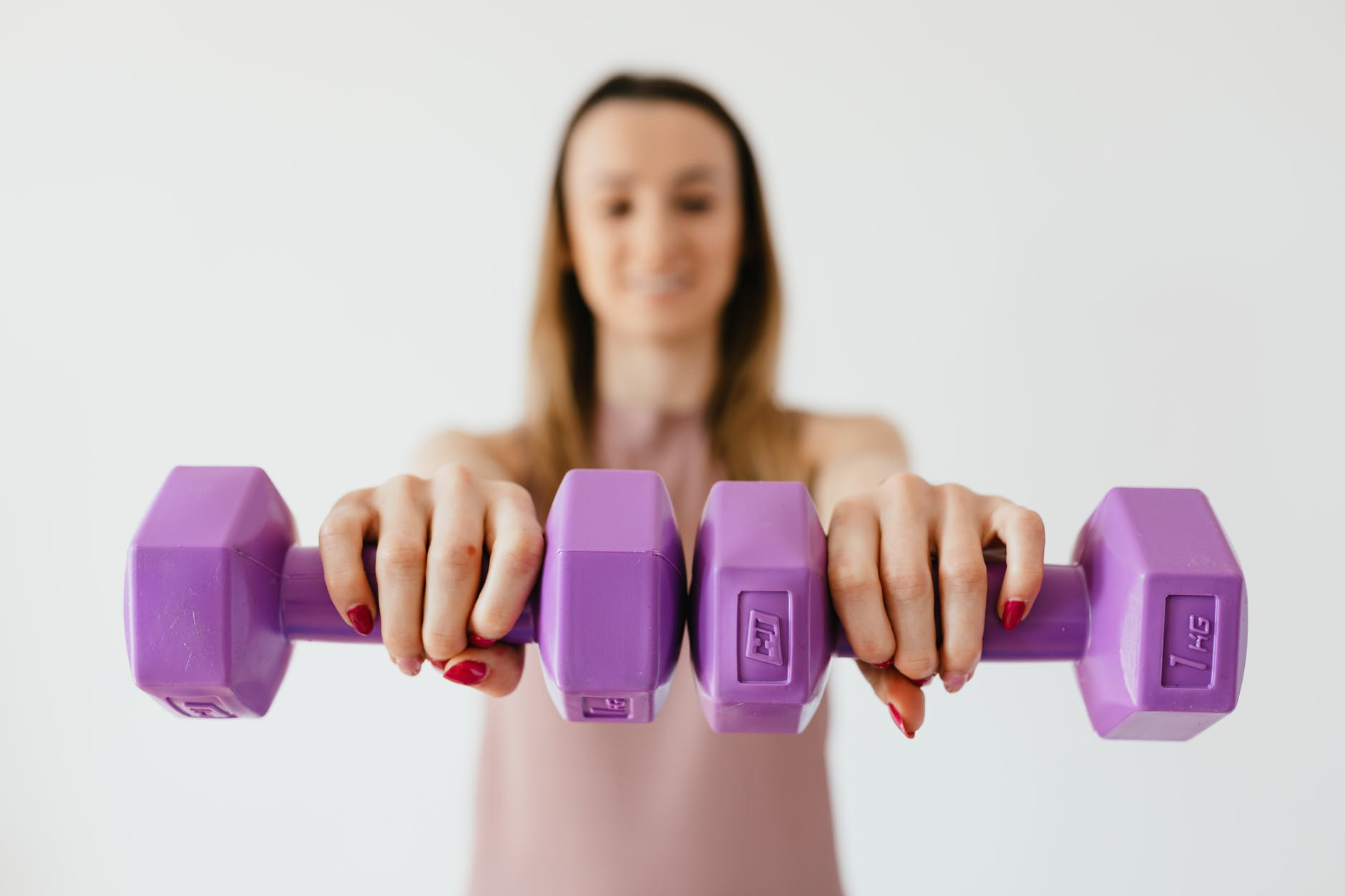 purple dumbbells in hands of positive sportswoman