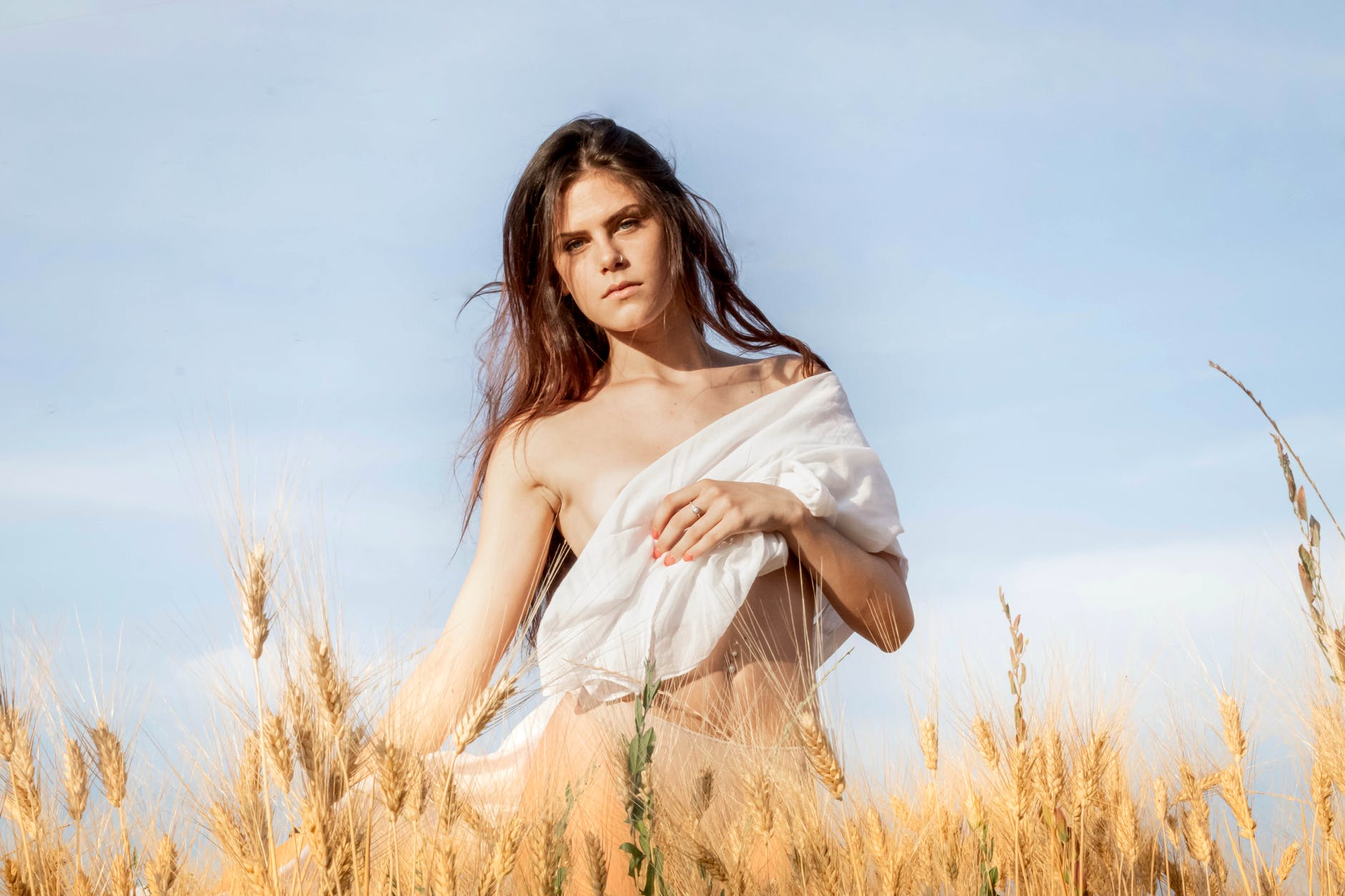young woman standing in field with cloth on breast