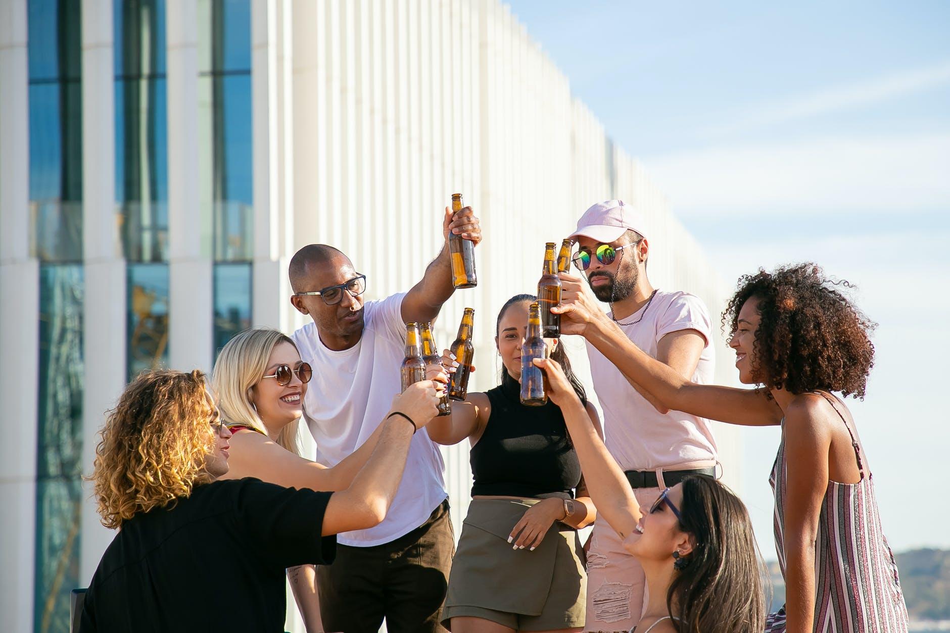 joyful diverse friends clinking beer bottles on rooftop