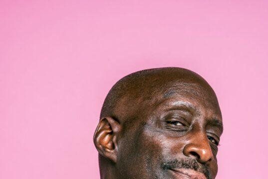 bald man wearing a pink t shirt