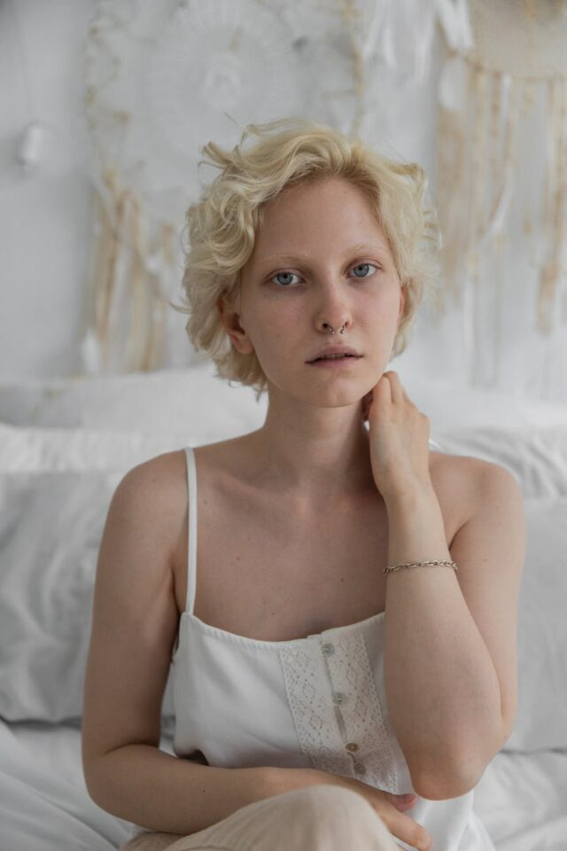 charming woman with short curly hair on bed