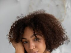 gentle black female with curly hairstyle in bedroom